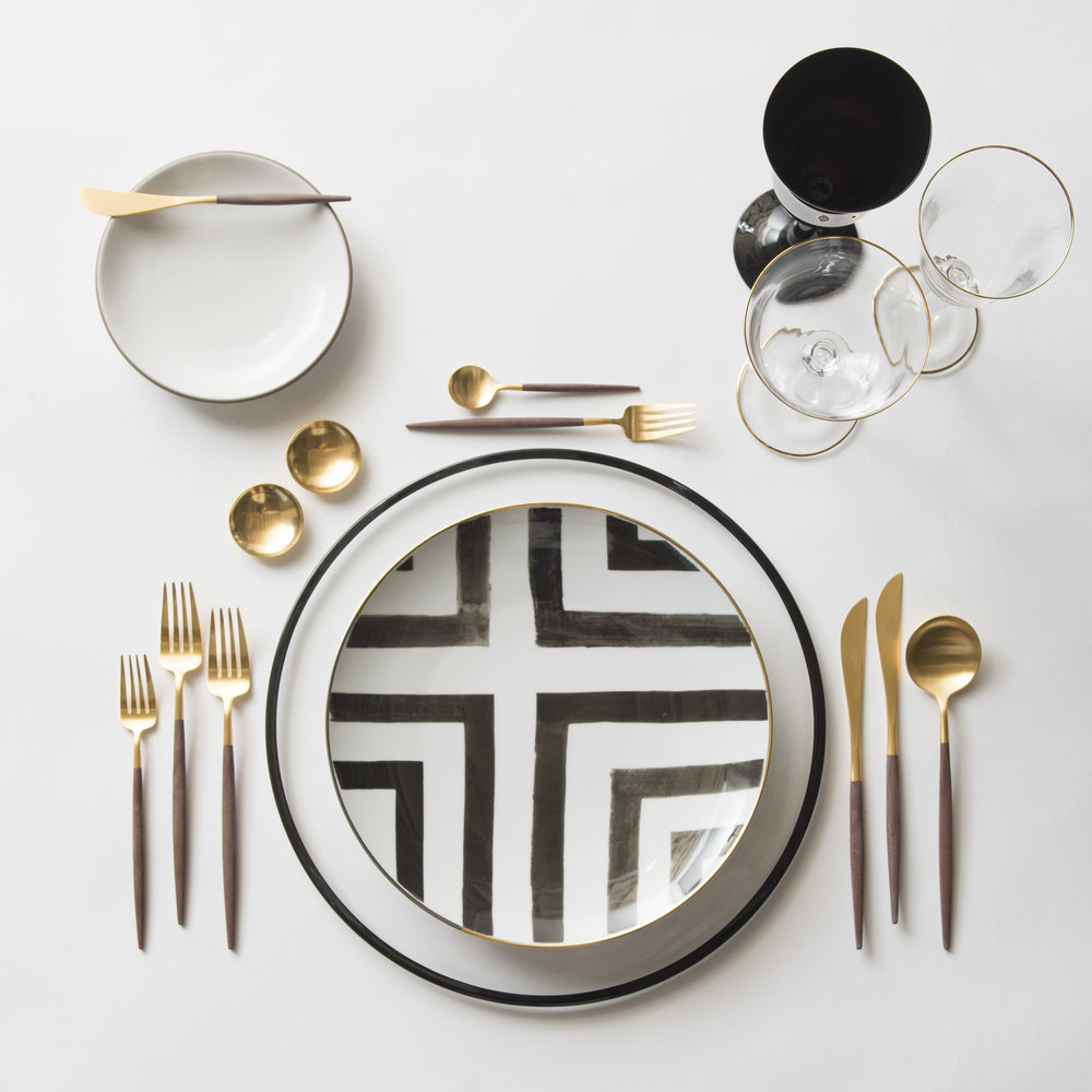 RENT: Halo Glass Chargers in Black + Heath Ceramics in Opaque White + Christian Lacroix Sol Y Sombra Dinnerware + Goa Flatware in Brushed 24k Gold/Wood + Chloe 24k Gold Rimmed Stemware + Chloe 24k Gold Rimmed Goblet in Black + 14k Gold Salt Cellars  SHOP: Halo Glass Chargers in Black + Goa Flatware in Brushed 24k Gold/Wood + Chloe 24k Gold Rimmed Stemware + 14k Gold Salt Cellars