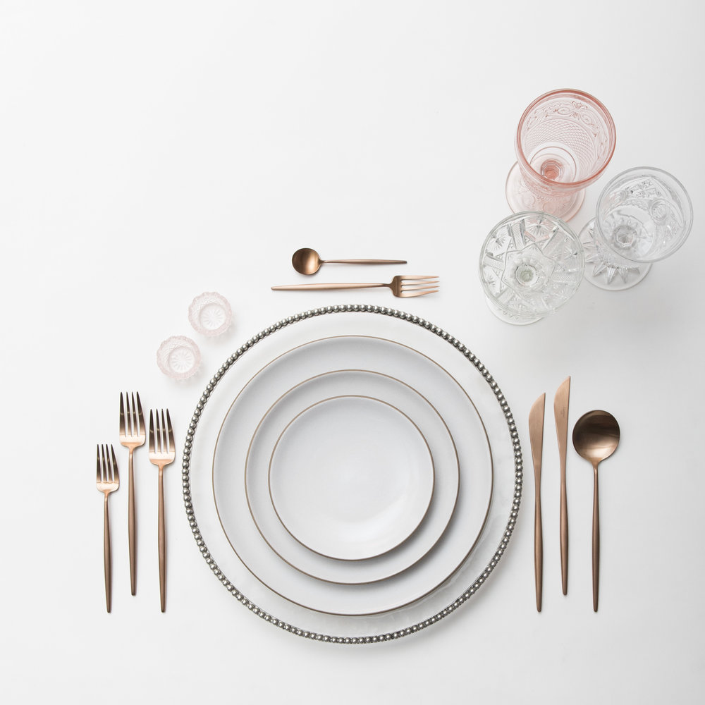 RENT: Pavé Glass Chargers in Pewter + Heath Ceramics in Opaque White + Moon Flatware in Brushed Rose Gold + Vintage Pink Goblets + Early American Pressed Glass Goblets + Vintage Champagne Coupes + Pink Crystal Salt Cellars   SHOP:  Moon Flatware in Brushed Rose Gold