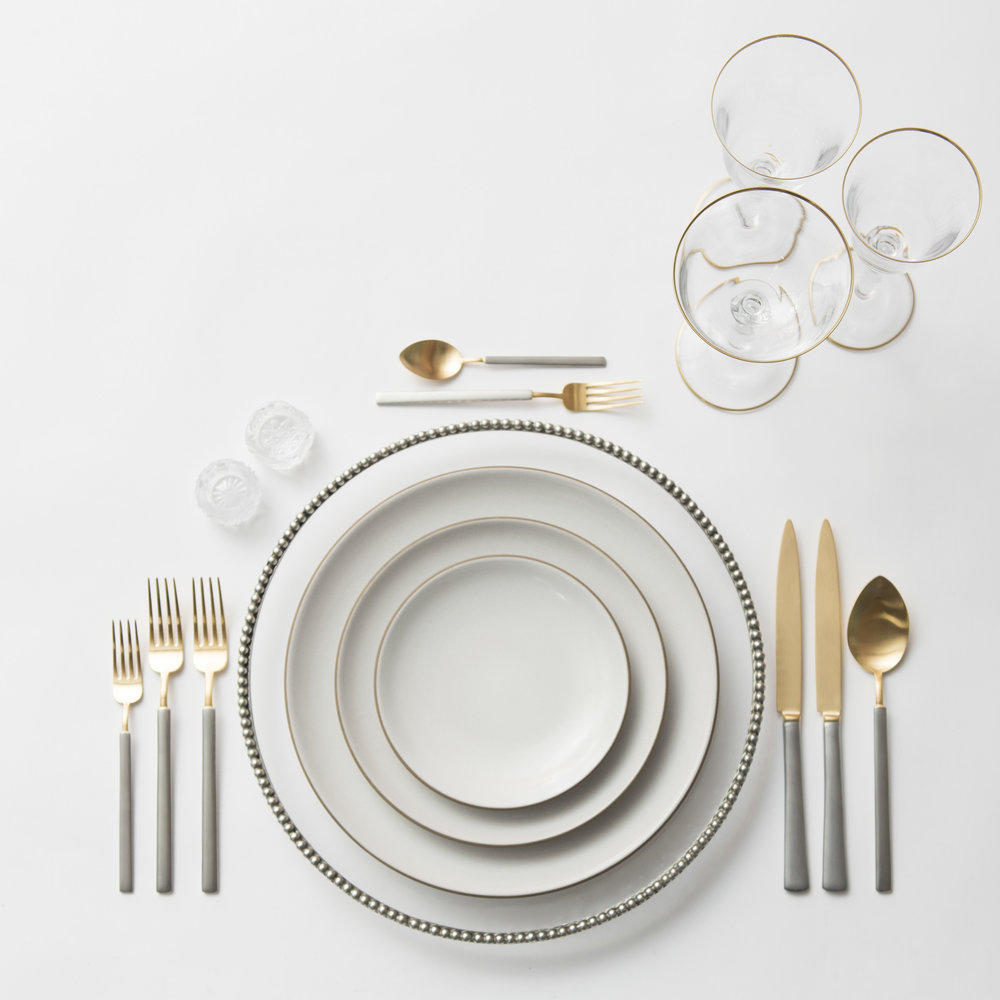 RENT: Pav é Glass Chargers in Pewter  + Heath Ceramics in Opaque White + Axel Flatware in Matte 24k Gold/Silver + Chloe 24k Gold Rimmed Stemware + Antique Crystal Salt Cellars  SHOP: Chloe 24k Gold Rimmed Stemware