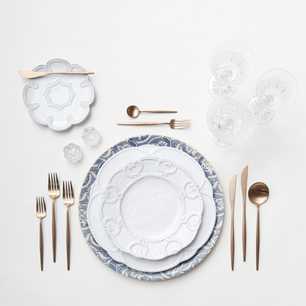 RENT: Blue Fleur de Lis Chargers + Signature Collection Dinnerware + Moon Flatware in Brushed Rose Gold + Czech Crystal Stemware + Antique Crystal Salt Cellars  SHOP: Moon Flatware in Brushed Rose Gold