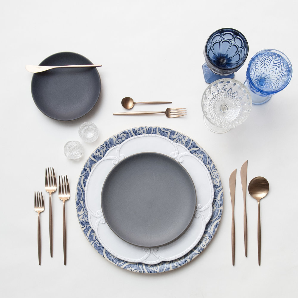 RENT: Blue Fleur de Lis Chargers + Signature Collection Dinnerware + Heath Ceramics in Indigo/Slate + Moon Flatware in Brushed Rose Gold + Dark Blue/Light Blue Vintage Goblets + Vintage Champagne Coupes + Antique Crystal Salt Cellars  SHOP: Moon Flatware in Brushed Rose Gold