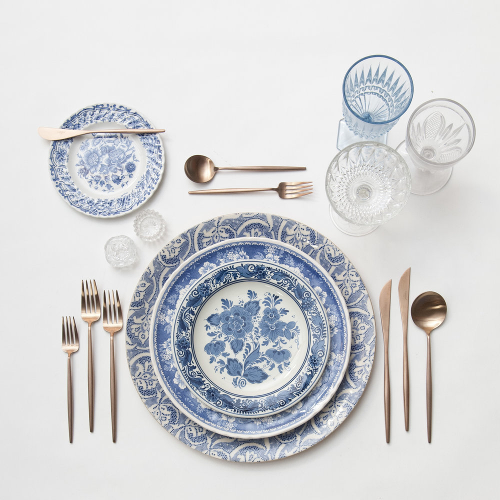 RENT: Blue Fleur de Lis Chargers + Blue Garden Collection Vintage China + Moon Flatware in Brushed Rose Gold + Light Blue Vintage Goblets + Early American Pressed Glass Goblets + Vintage Champagne Coupes + Antique Crystal Salt Cellars   SHOP: Moon Flatware in Brushed Rose Gold