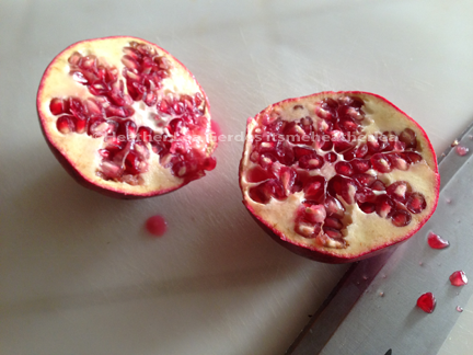 2 halves of pomegranate with knife and stray seeds