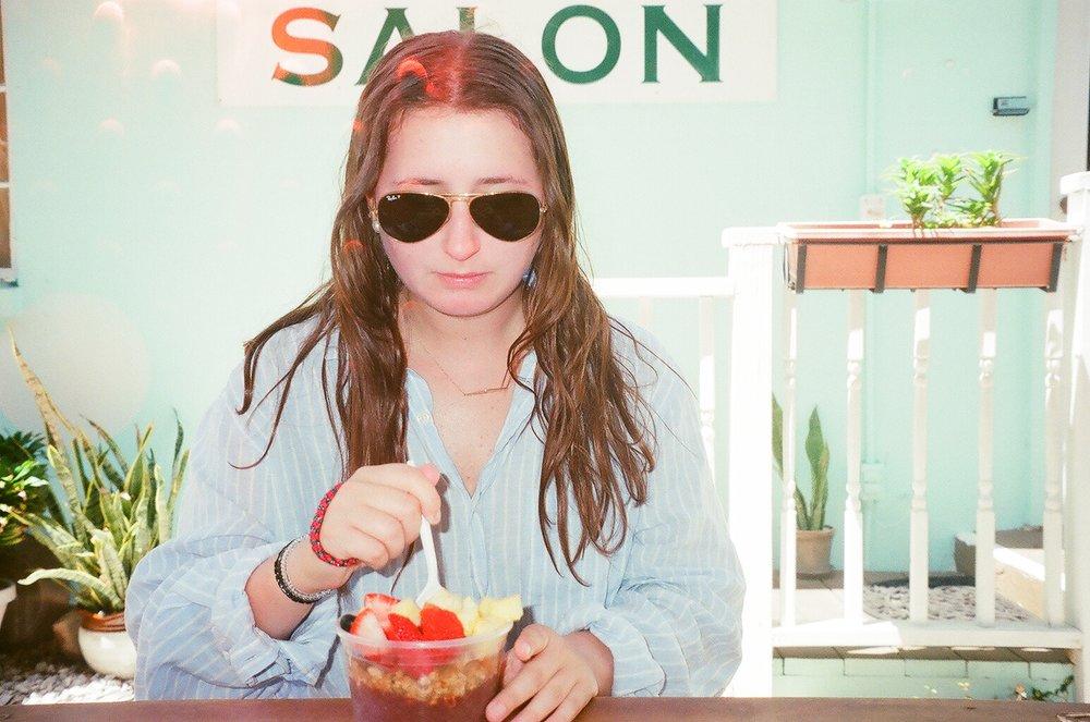 Zoe eating an açaí bowl from Surf Shack