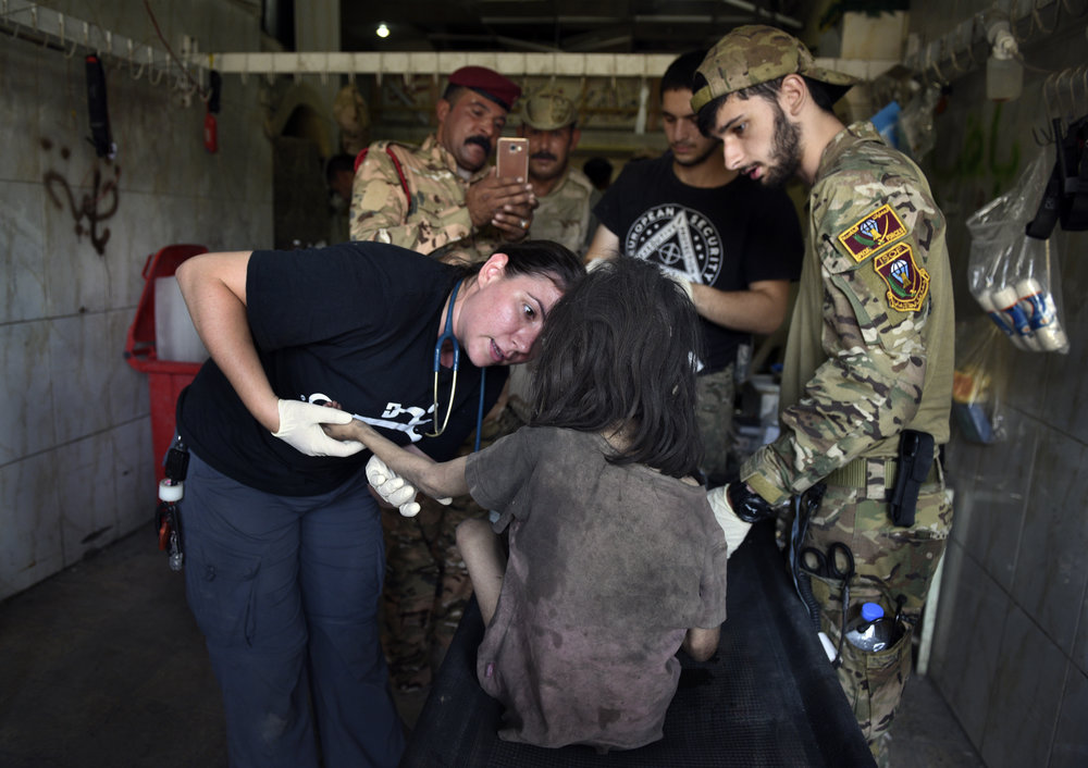 Global Response Management Team Members administering emergency trauma care during conflict in Iraq
