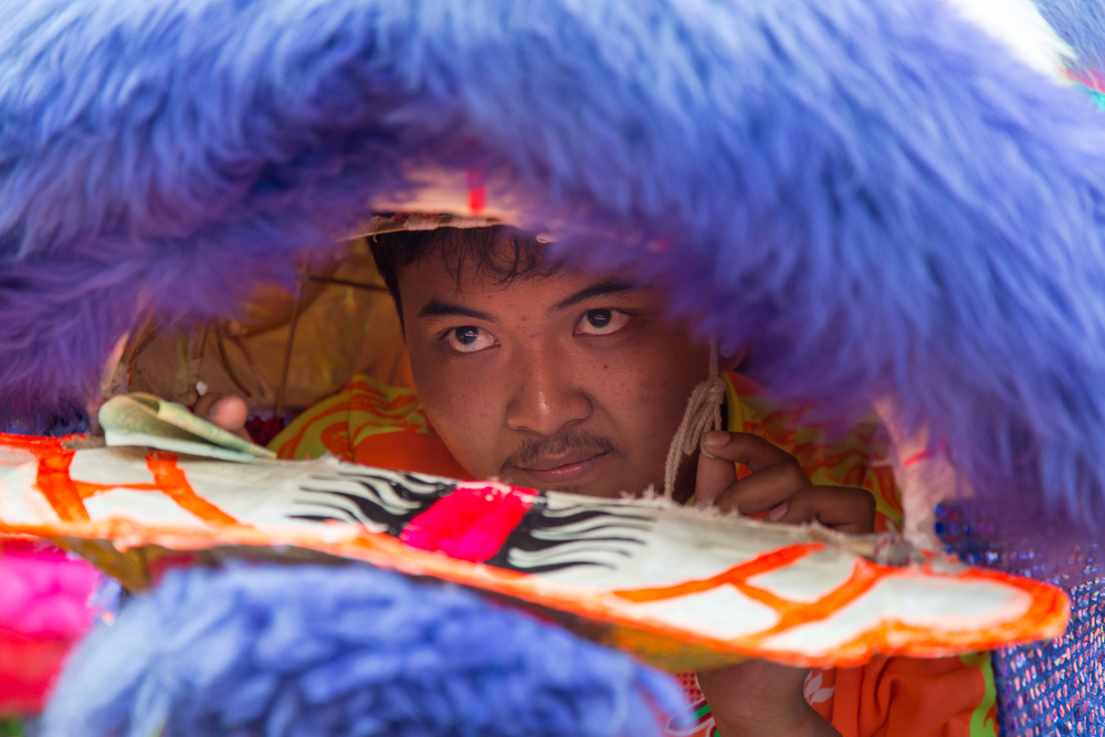 A performer keeps intense focus while operating the dragon's mouth using a string in his left hand.
