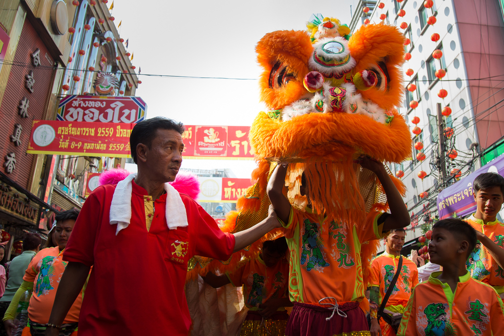 The young performer in orange dragon is guided down the busy street.