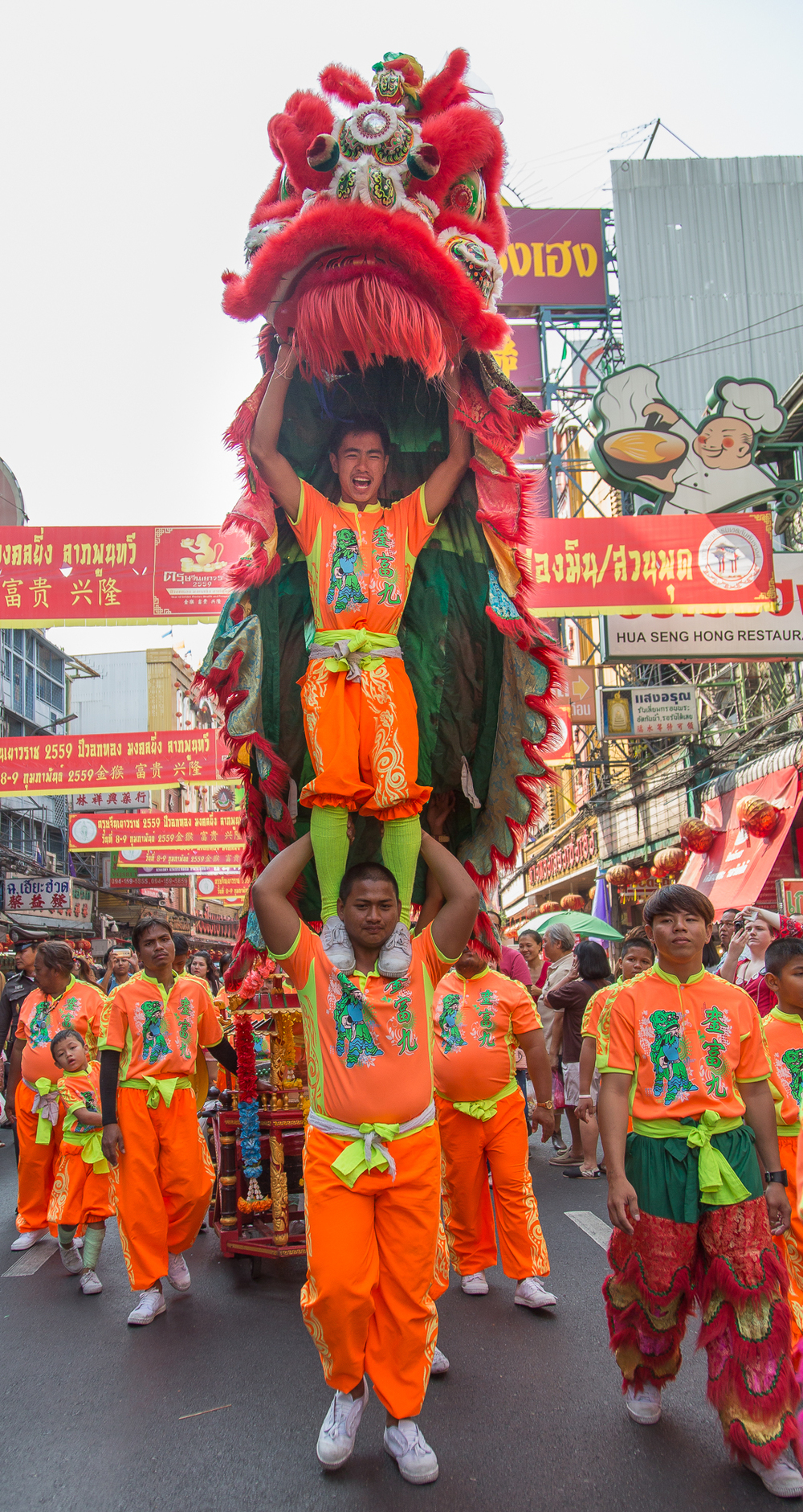 A performer triumphantly holds his costume in the air as he stands on the shoulders of an assistant.