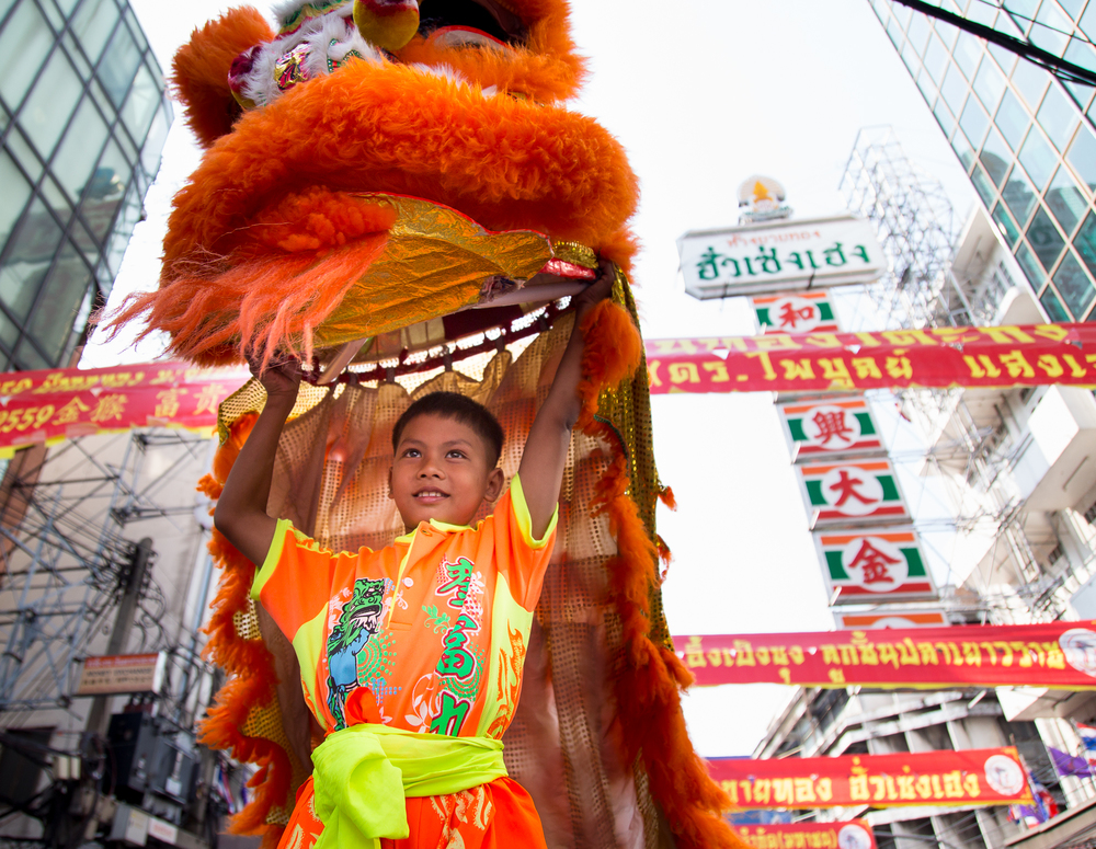 A young performer proudly holds his costume above his head while standing on the shoulders of an assistant.