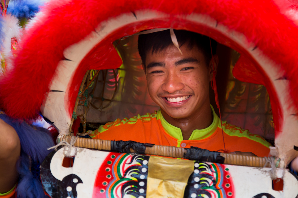 A performer takes a brief break and smiles during the procession.