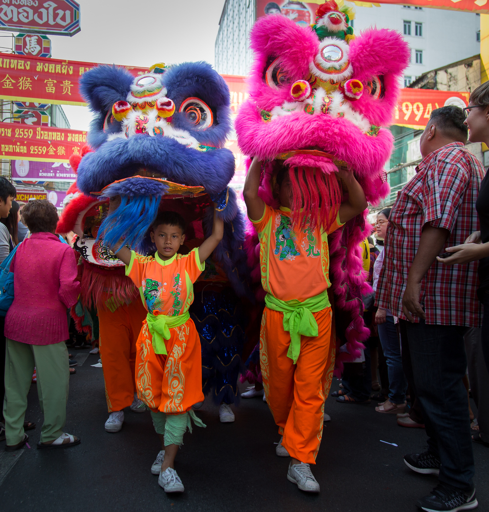 The blue and pink dragons walk together step-in-step through the crowd.