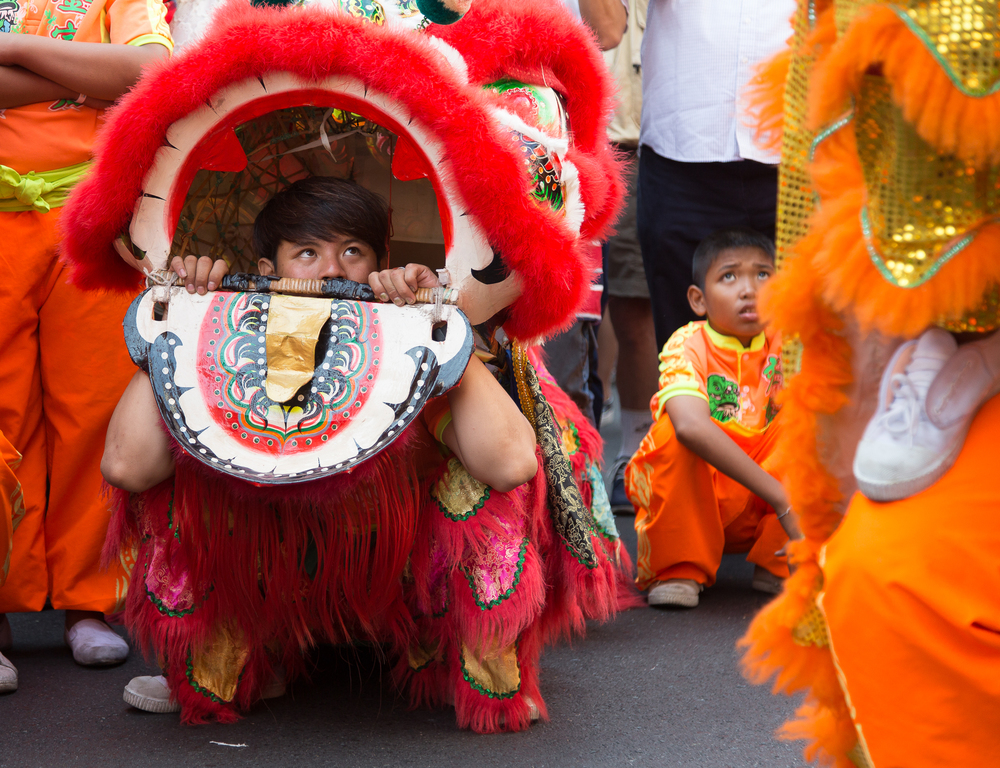 The red dragon patiently waits his turn to dance while watching the others perform.