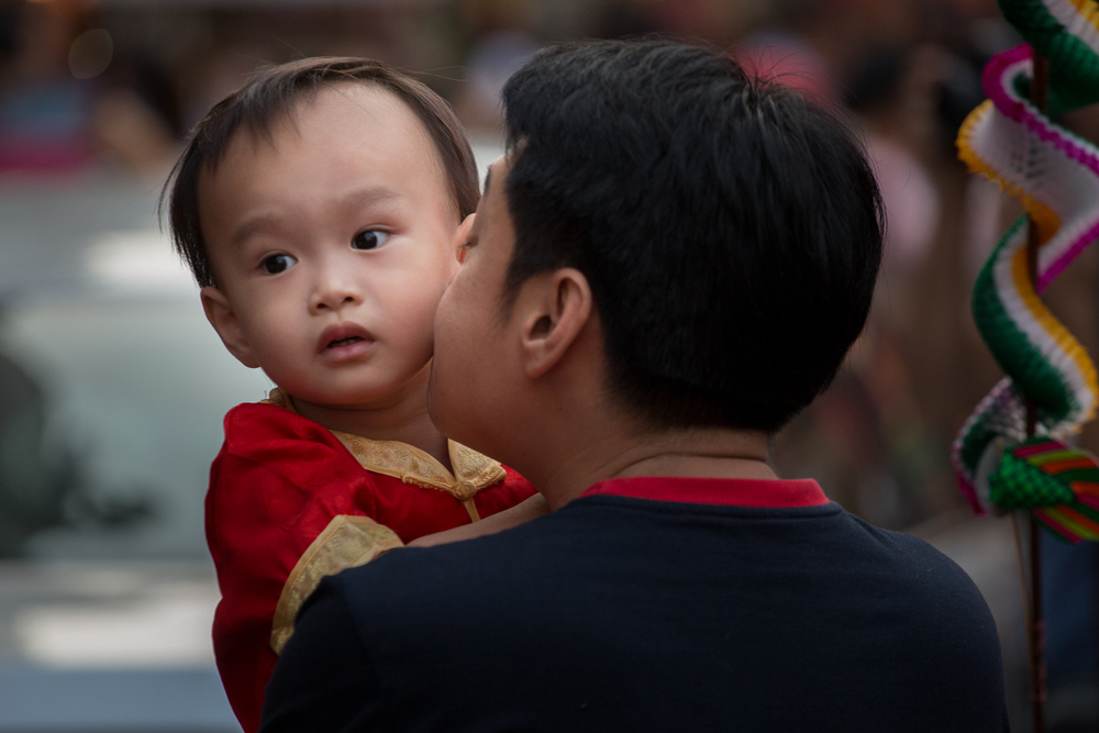 A father kisses his child on the cheek during New Year's festivities.