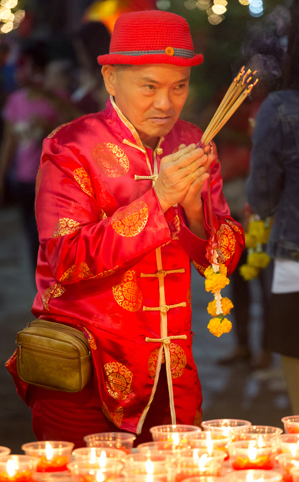 Raat, a Bangkok native, prays and holds lighted incense he intends to give as an offering in Wat Mangkon Kamalawat on the eve of the Lunar New Year.