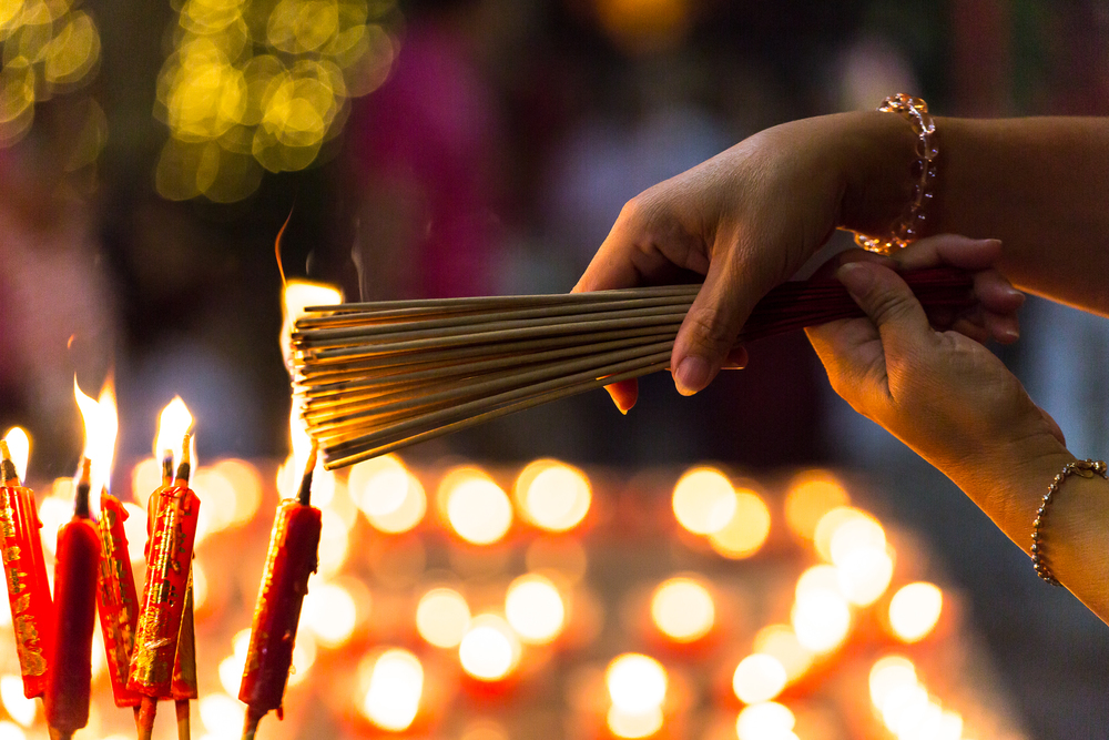 A woman lights incense at a Buddhist temple in Bangkok's Chinatown on the eve of the Lunar New Year.