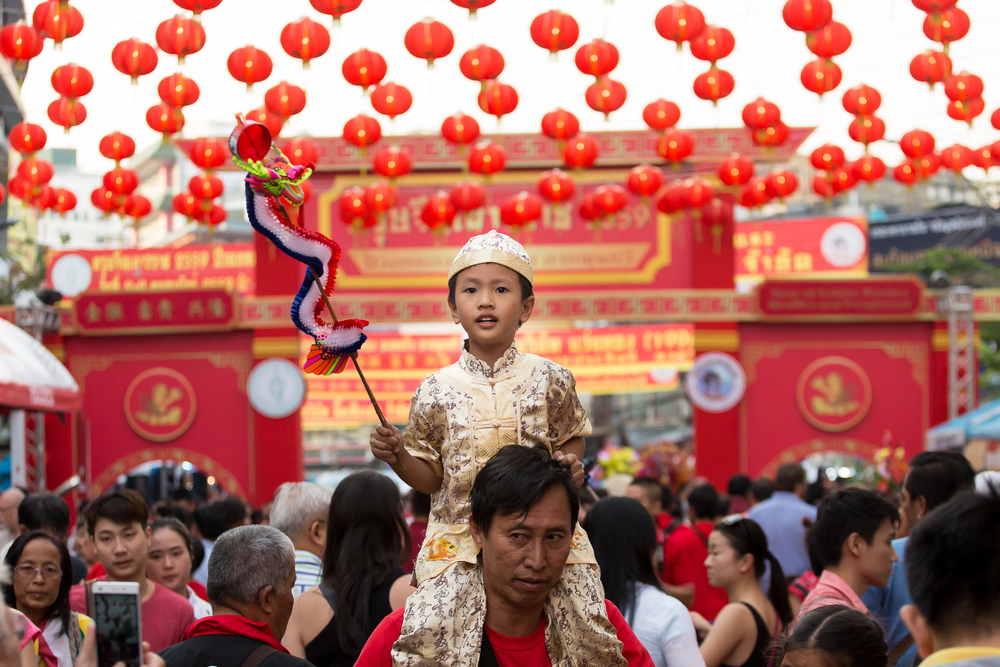 A young child sits on the shoulders of his father in the crowded  main street of Bangkok's Chinatown.