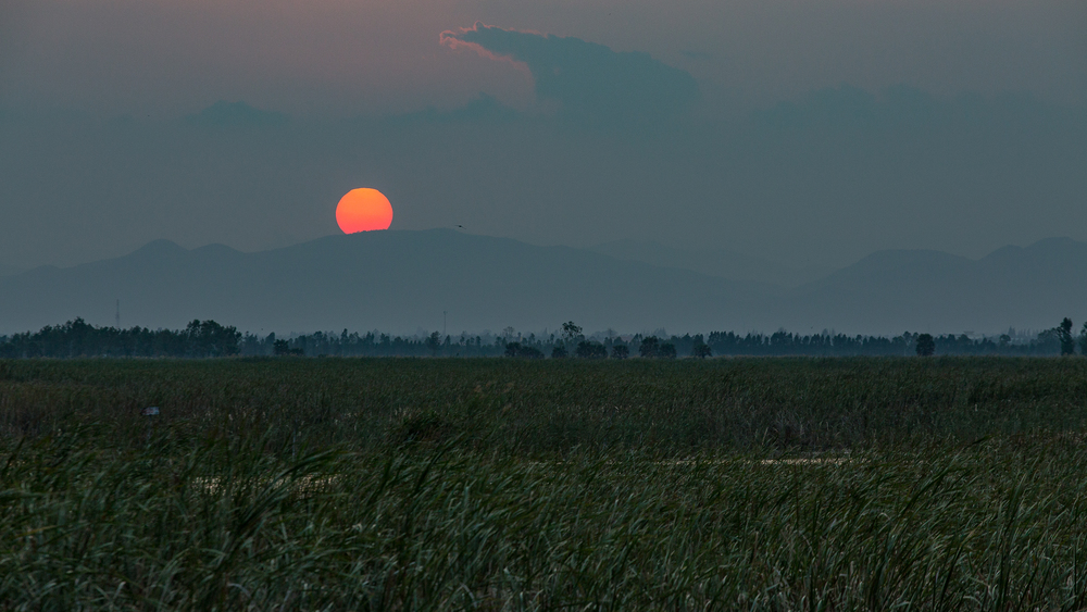 The Sun sets behind a mountain overlooking Thung Sam Roi Yot Wetlands.