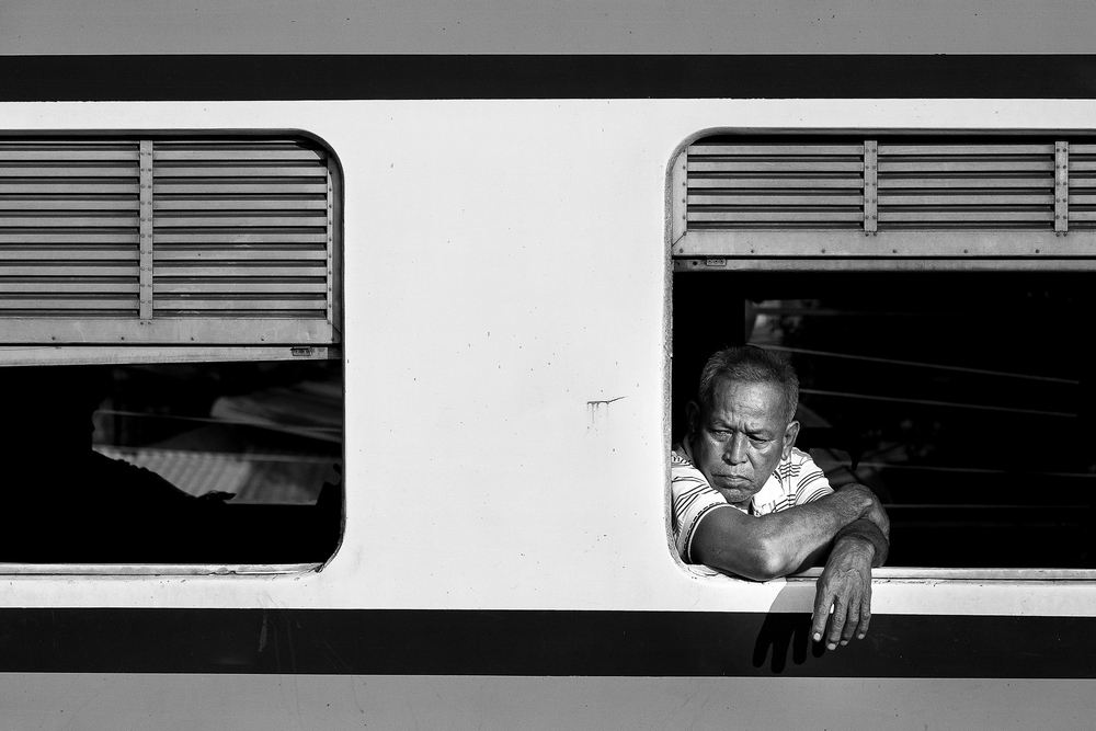 Some of my best/favorite photos have come from train stations. Train travel seems to bring together an interesting combination of characters, and many of them wear their emotions. I snagged this photo of a train passing by in the opposite direction. What does this man's expression convey to you?