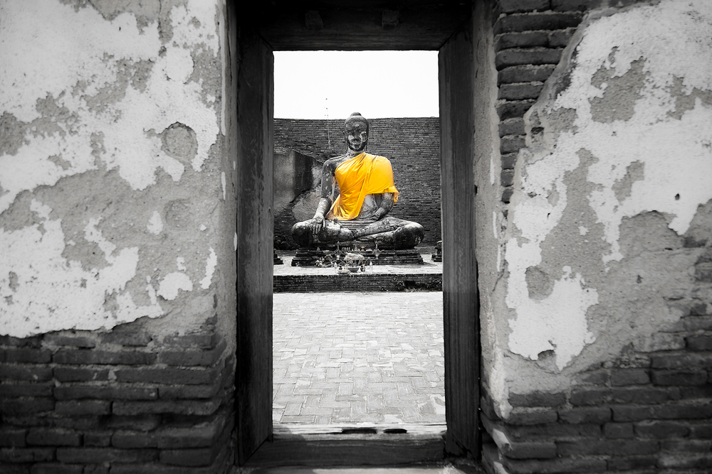 A statue of Buddha sits in the ruins of a wat.