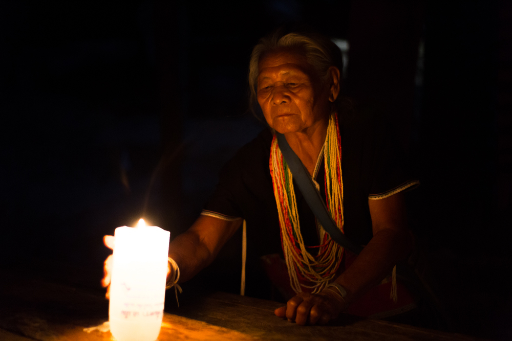 Not all of the people in villages have access to electricity. This woman lights a candle on a table for illumination at night.