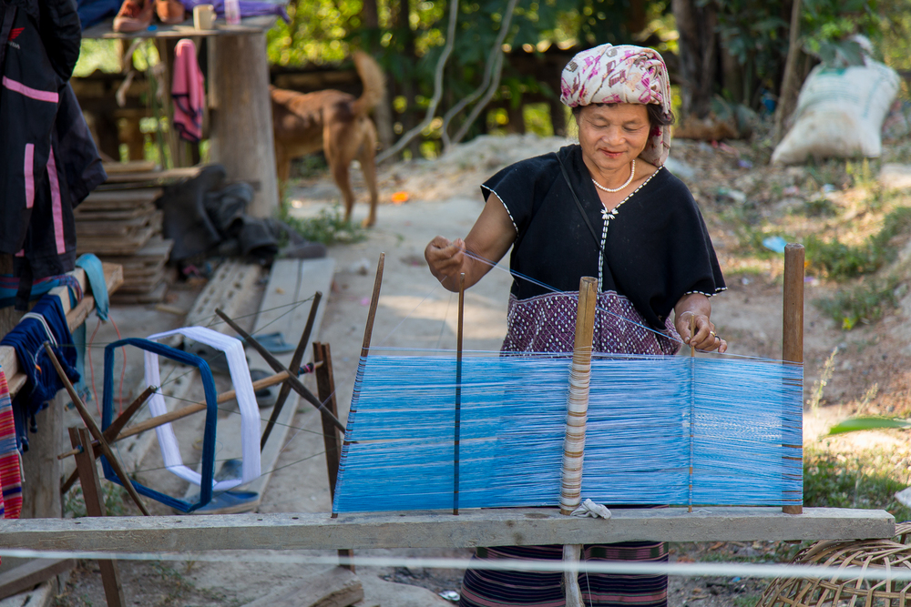 A woman weaves fabric by hand. The end product will be a skirt. Many of the clothes worn by people in these villages was made with their hands.