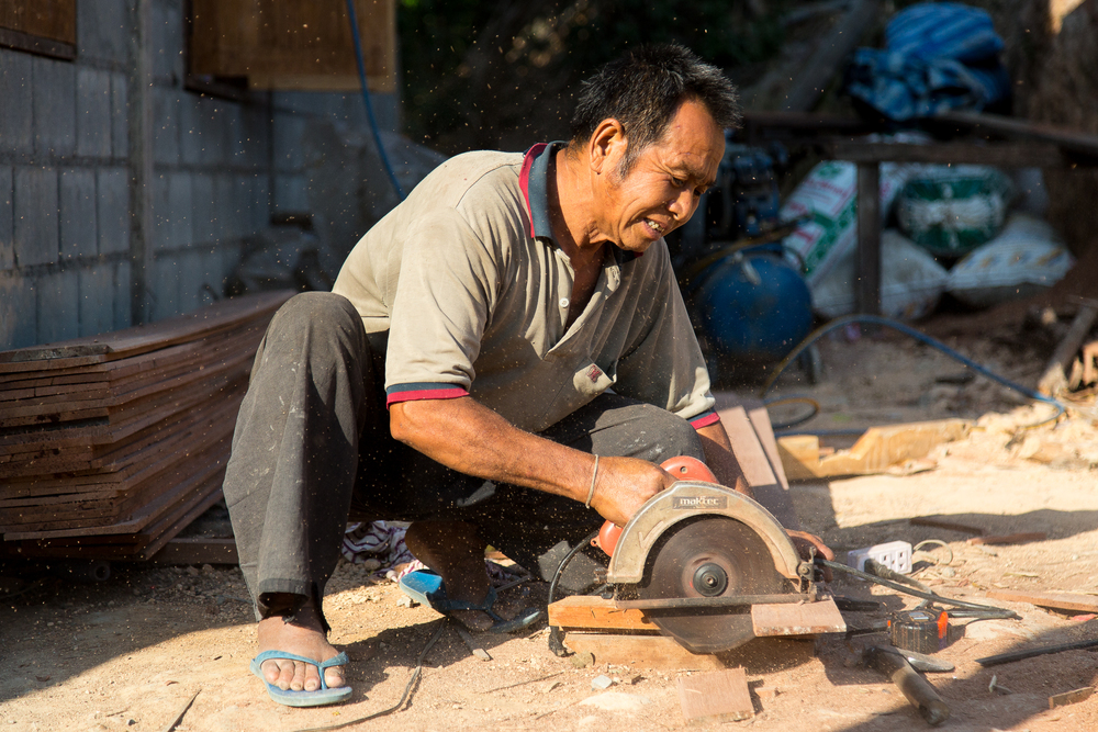 A man uses a power saw to cut wood for making a home in the village.