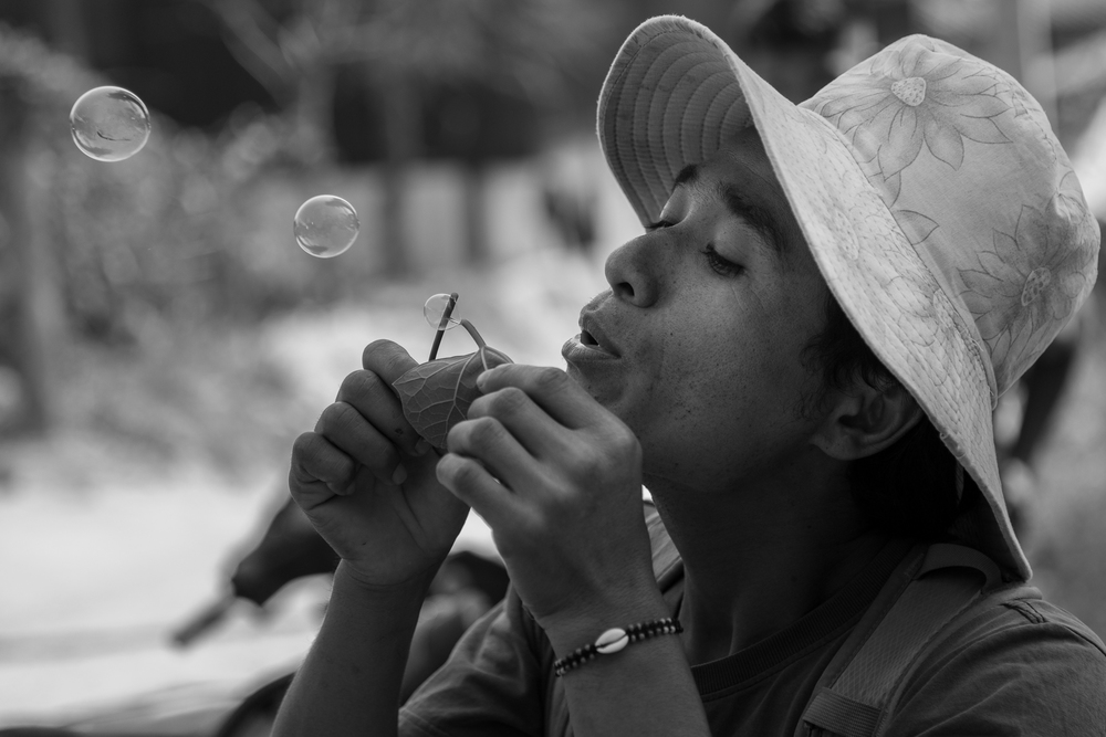 Thama, my guide, knows all the tricks of the jungle. In this image, he's using a mango leaf to blow bubbles.