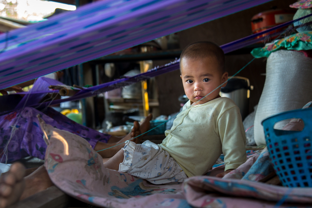 A child sits beneath the cloth that is being woven by his mother.