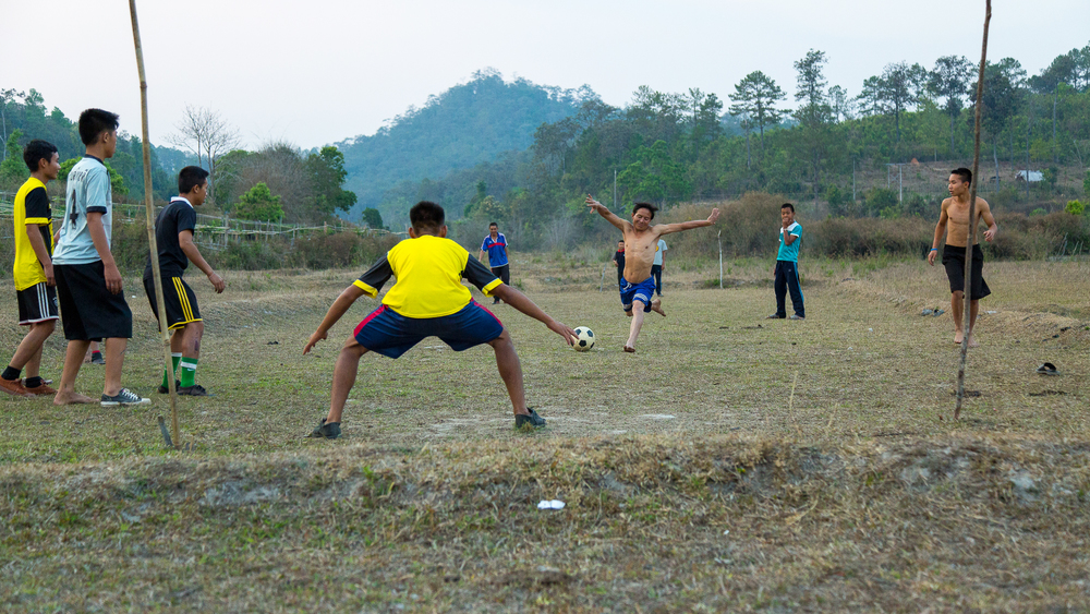 A group of men from a village play soccer in a dried rice paddy.