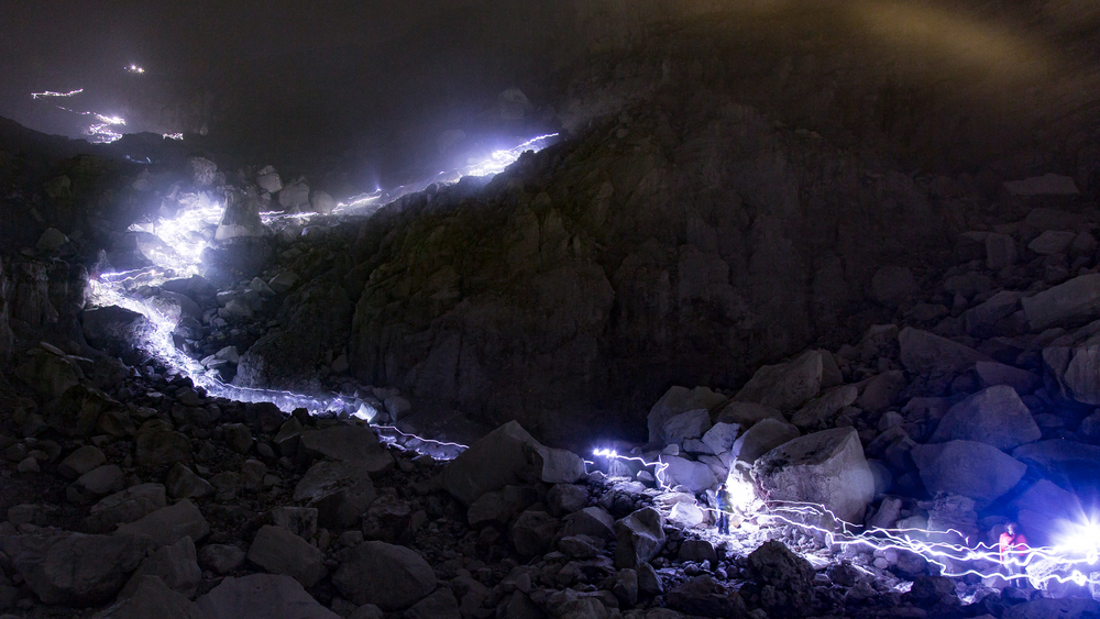 Hundreds of tourists flock down the crater wall at 3 AM to witness the blue flame. Hundreds of headlamps illuminate the path on the crater wall.