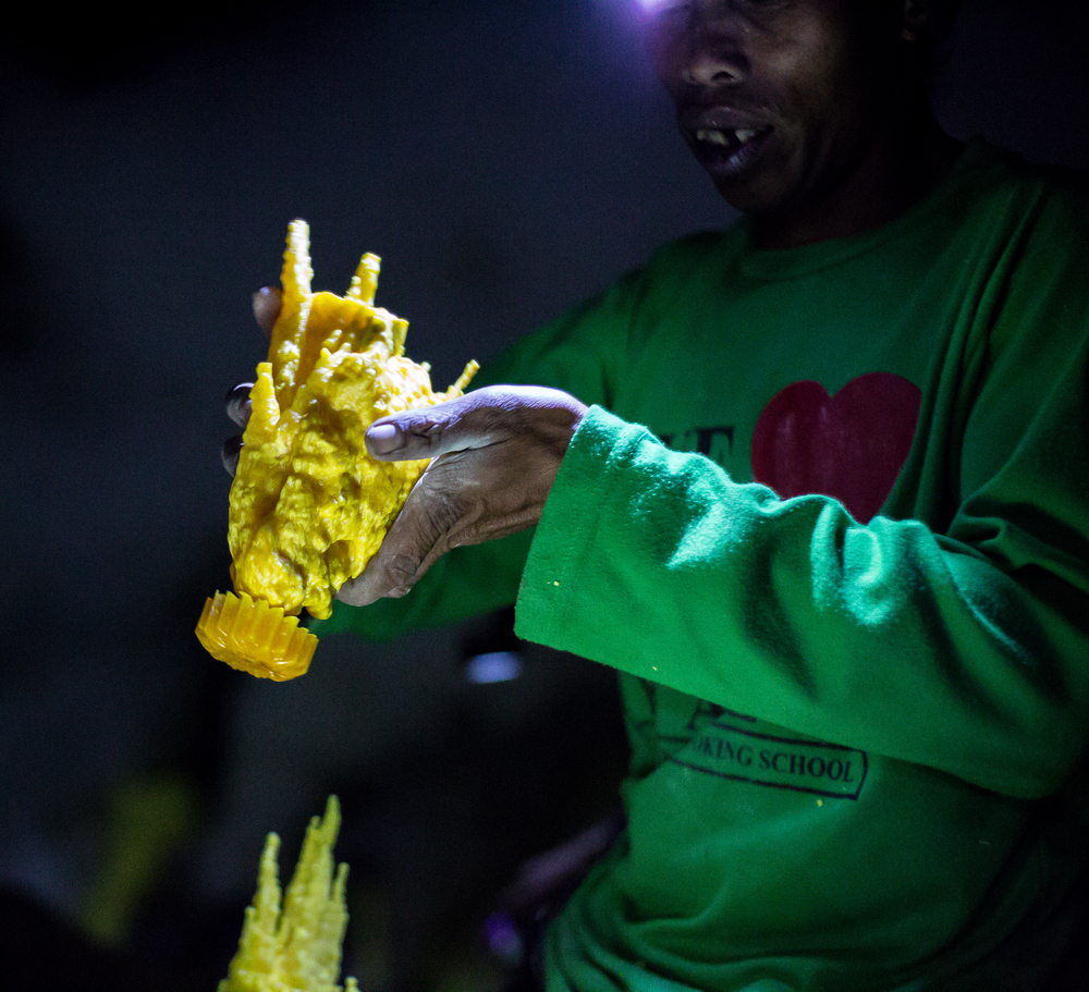 Mariono lifts up one of his sulfur sculptures.