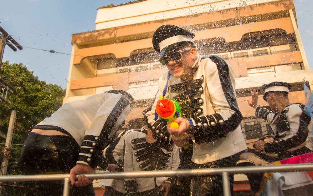 A man in uniform gets soaked while firing his squirt gun from the back of a truck.