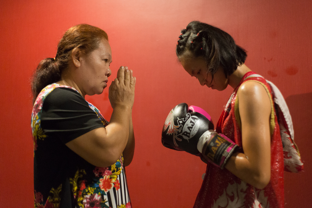 Sai   prays with her mother shortly before the match. The culture of Muay Thai boxing is steeped in Buddhism, and this prayer routine takes place before every fight. Sai   started boxing because one of her friends invited her to come to the gym. Once Phom saw her potential, he asked if she wanted to fight. She now competes semiprofessionally and hopes to become a famous boxer.