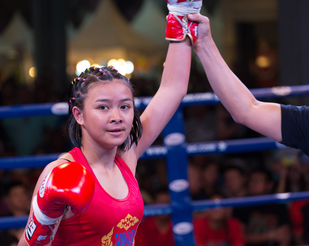 After knocking out her opponent,   First   proudly stands in the center of the ring with her hand held high as she's declared the winner by the referee. In the future, she wants to become a fighter full-time and become famous internationally. Phom, her trainer, said   First is   well on her way to achieving this goal. Months after this photograph was taken, First had her first international fight in Singapore in June, 2016.