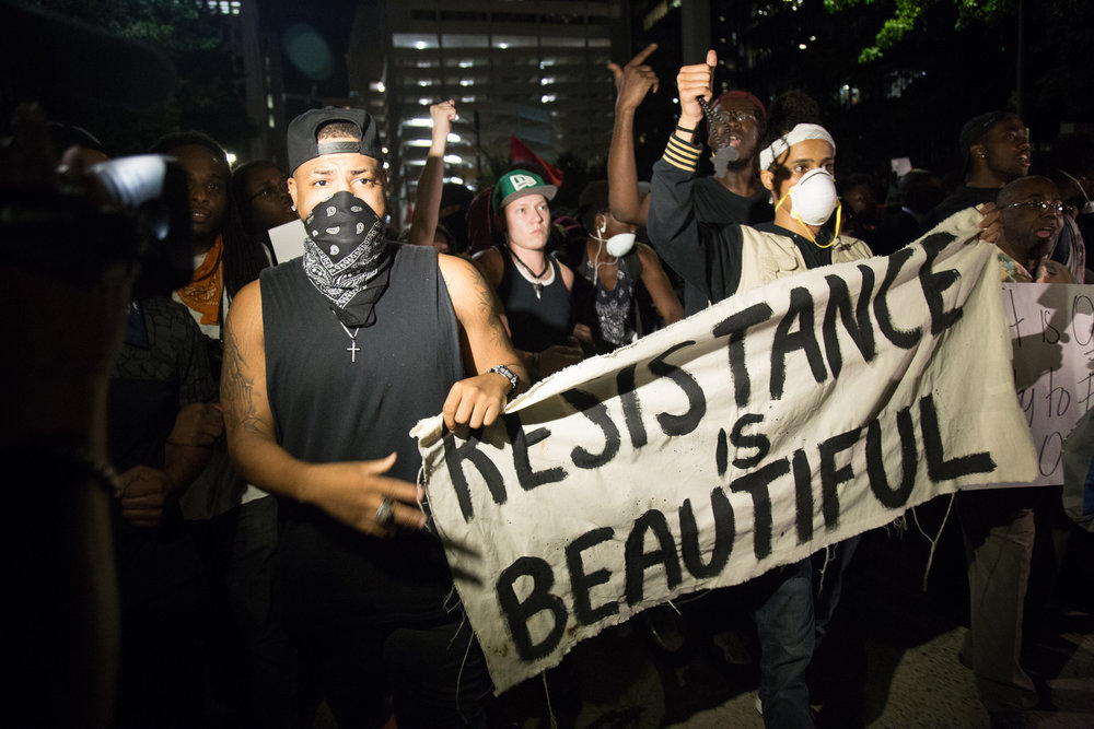 "Two protesters marching in Charlotte on Thursday, Sept. 22nd, 2016, carry a banner that reads ""RESISTANCE IS BEAUTIFUL."" One wears a bandanna over his face, and the other wears a mask."