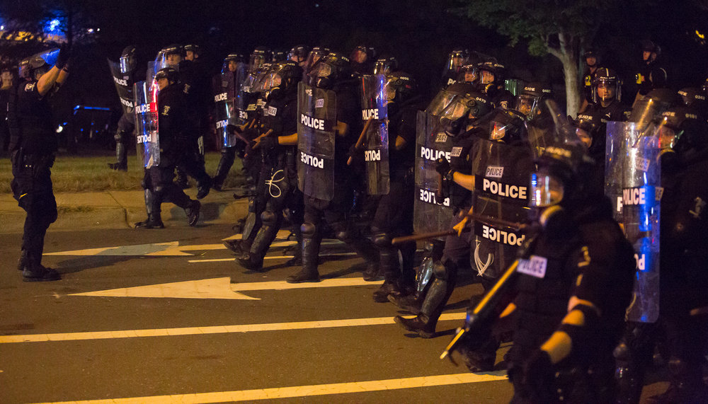 Police in riot gear walk in a line to push back protesters and keep Interstate 277 clear on Thursday, Sept. 22nd.