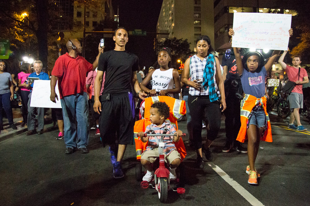 A family pushing a child in a stroller lead a group of protesters during a march on Saturday, Sept. 24th.