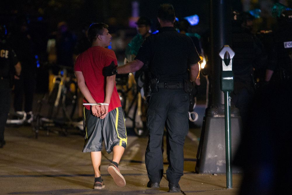A man is arrested early in the morning on Sept. 24th for breaking the midnight curfew. Police allowed protesters to stay on the streets hours after midnight and gave multiple warnings to disperse.
