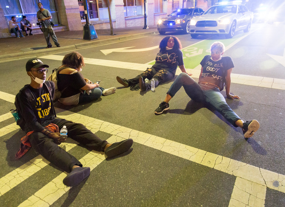 A group of protesters sit in the middle of the street after a long night of marching on Sept. 23rd. They're two hours past the midnight curfew, and cops are preparing to begin arrests.
