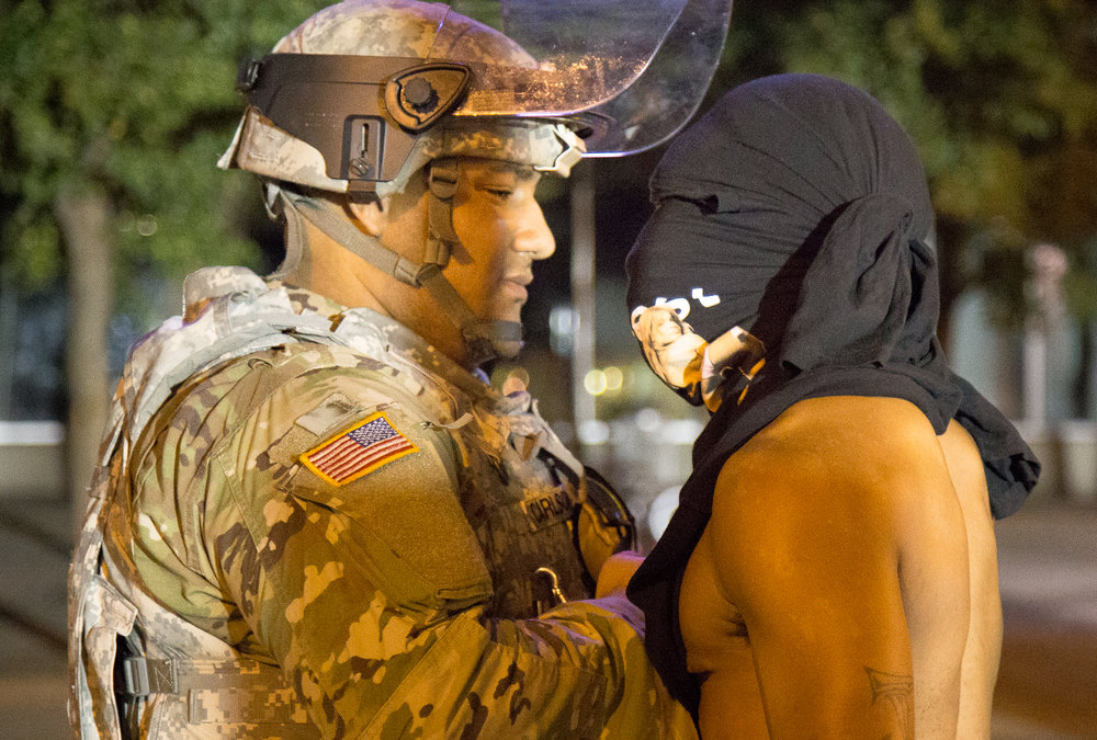 A protester pushes his chest against a National Guard soldier during a confrontation on Saturday, Sept. 24th.