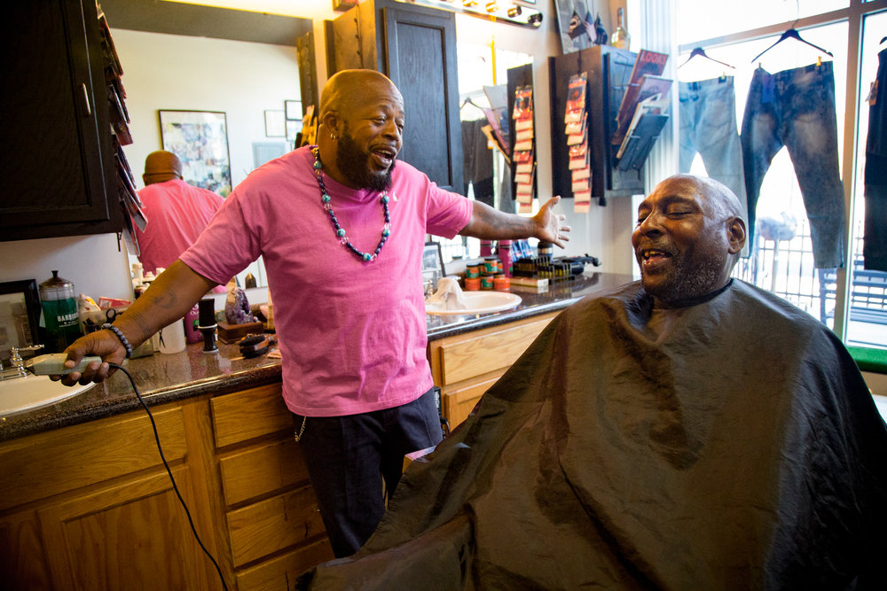 Samuel Jenkins jokes with Fred Spain as he gets a haircut in Jenkins' barber shop on    Angier Avenue in Durham, NC.