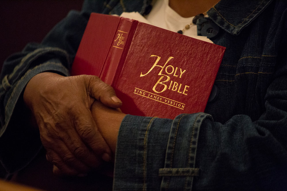 Annie Williams holds her Bible close to her chest during Bible study on a Wednesday night at Antioch Baptist Church in Durham, NC.