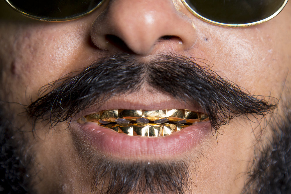 Jabar Zazal poses for a portrait and wears a grill as part of his Post Malone costume on Halloween Tuesday, Oct. 31, 2017, on Franklin Street in Chapel Hill.