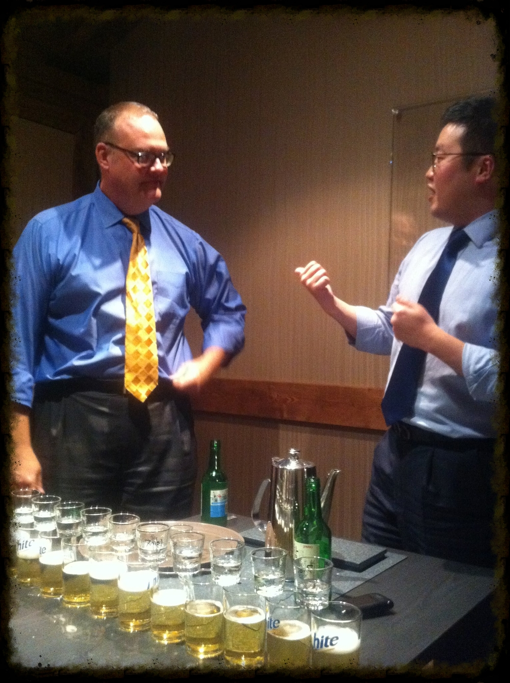 "One of my team members explaining the chain-reaction ""bomb shot"" during my welcome dinner. I had to use the metal chopsticks to tap the first shot of balanced   soju  , causing a domino effect so that each shot would fall into its glass of beer, creating the ""bomb shots,"" which you down in one gulp."