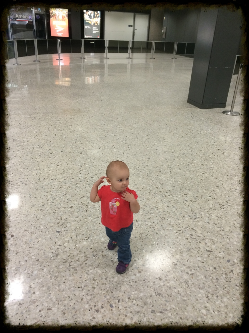 Reunion! A tiny Annabelle deplanes, somewhat stunned, in the gaping Dulles Airport arrivals area after a 12-hour flight from Seoul and half of her first year apart from her Dad. She looks pretty good, considering.