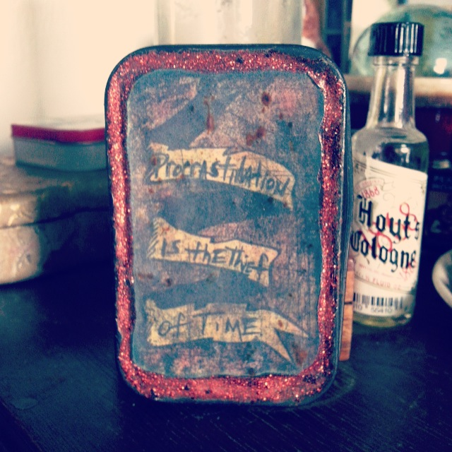 """Altoids tin repurposed and painted by Papa Toad Bone as a tiny St. Expedite prayer box/altar. It reads: """"Procrastination is the thief of time."""""""