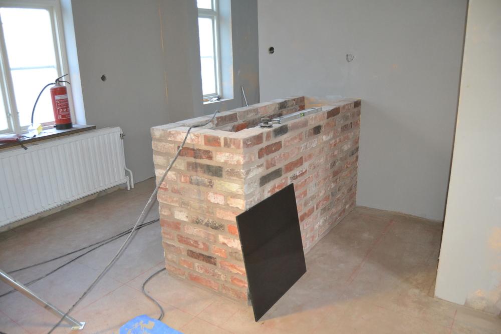 På återvinningscentralen i Malmö hittade vi likadan tegel som på väggen vi knackade fram. Av det byggde vi vår köksbar.  Golvet var ett projekt i sig;-). Värmeslingor skulle läggas, golvet skulle flytas och stora granitplattor skulle läggas...