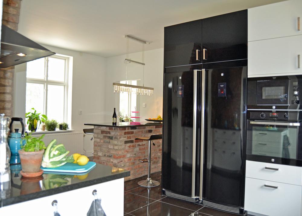 Både bänkskivor och skivan på köksön är i svart granit...