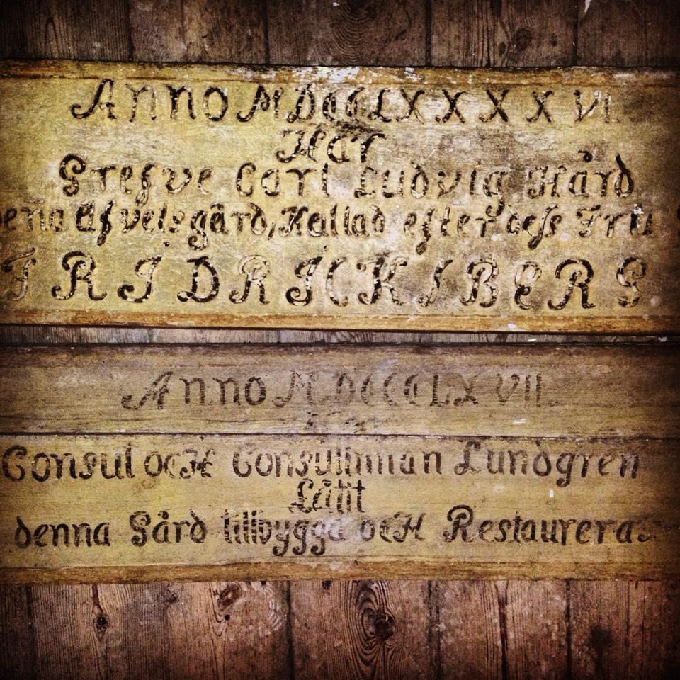 """Den översta tavlan är den äldsta. Den är tillverkad av en mycket bred ekplanka och är också den som är i allra bäst skick - i princip helt intakt. På den tavlan står det: """"Anno 1796 har Grefve Carl Ludvig Hård låtit bygga denna afvelsgård, kallad efter dess fru Grefvinna FRIDRICKSBERG""""."""