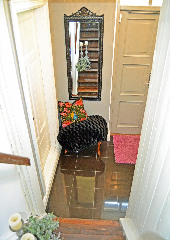 """Den här ingången ligger i anslutning till köket, men också intill de två rum i fil, som ligger längst ut på husets västergavel - och som utgör Louise """"lilla lägenhet"""". Så, av praktiska skäl, är det mest hon som använder denna entré.  När vi kom till Fredriksberg, såg denna hall rent bedrövlig ut... Jag förstår faktiskt inte hur man på så liten yta, kan få plats med så mycket fula material och ful inredning, hahaha. Bara den mörka, """"bubbliga"""" 60-talsdörren, stengolvet och alla hyllor, ja herre Gud...hahaha."""